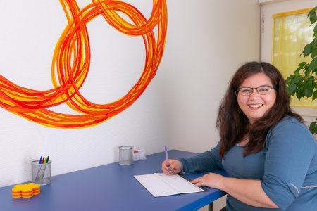 Katharina Schneider mit Kalender am Tisch
